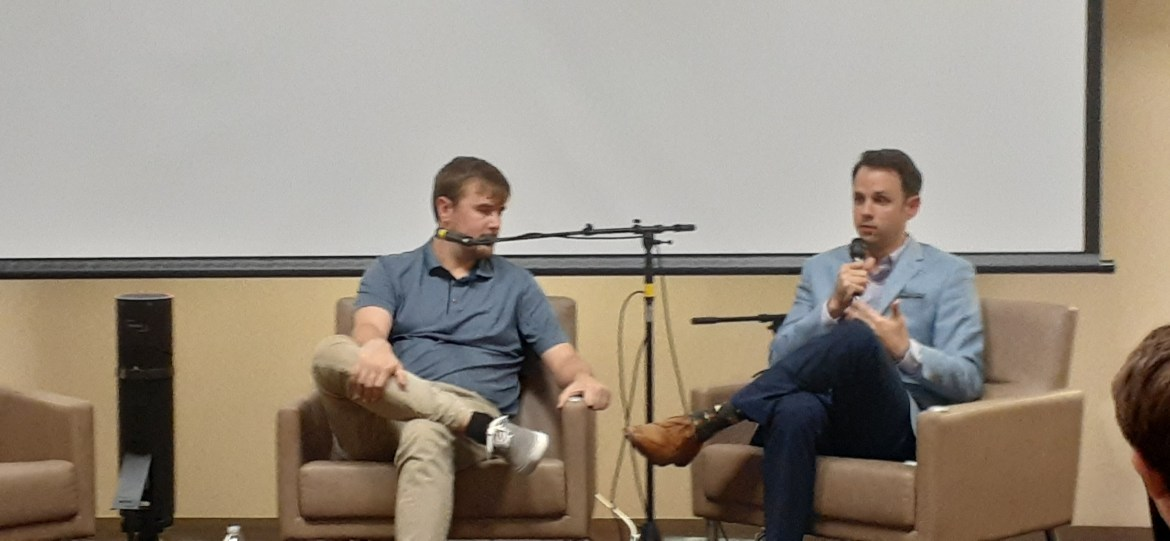 Two men sit in a wide seminar room. Lucas Haskins wears a blue polo while sitting in a chair with his legs crossed as he listens to Brant Freeman talk next to him. Brant Freeman speaks to the crowd.