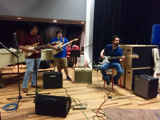 Two college students stand in a recording studio room, holding electric guitars and surrounded by amplifiers. A piano is behind them and there are microphones in place for recording. To their right sits Jose Garza, the faculty head of the Rock Ensemble, wearing a blue shirt and picking at an electric bass.