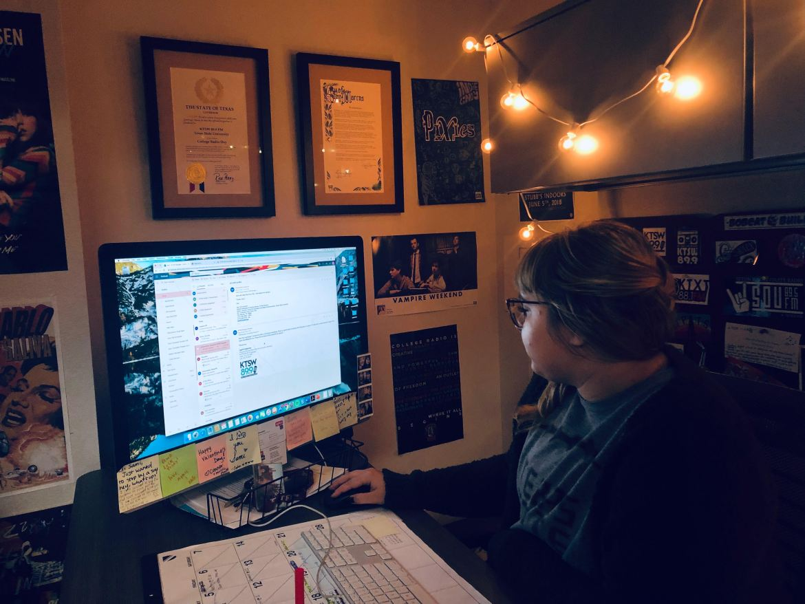 Sami responding to emails in her office with posters on the wall and hanging lights