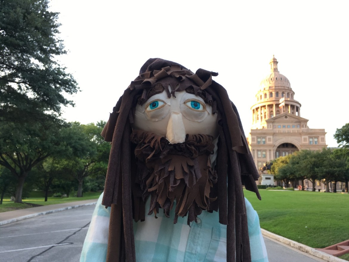 A puppet of a man with blue eyes and a brown beard and dreadlocks stands in the foreground, with the Texas State Capitol building visible in the background