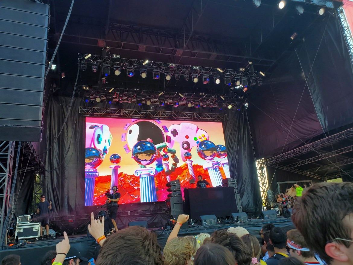 Troyboi performing at the T-Mobile stage at ACL. The backdrop is random objects, such as a yin-yang sign, glass balls on podiums, and game controllers.