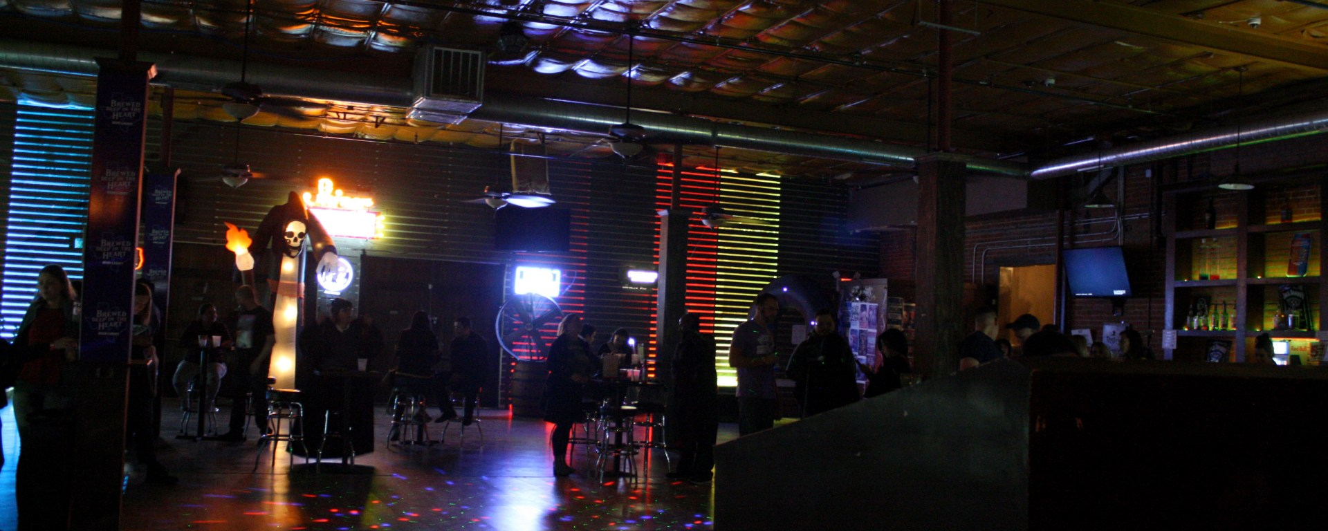 Several people stand around cocktail tables around concert venue space.