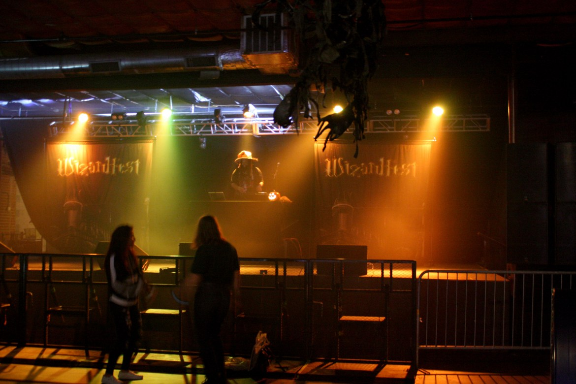 Two girls dance in front of a DJ booth that reads 'Wizardfest'.