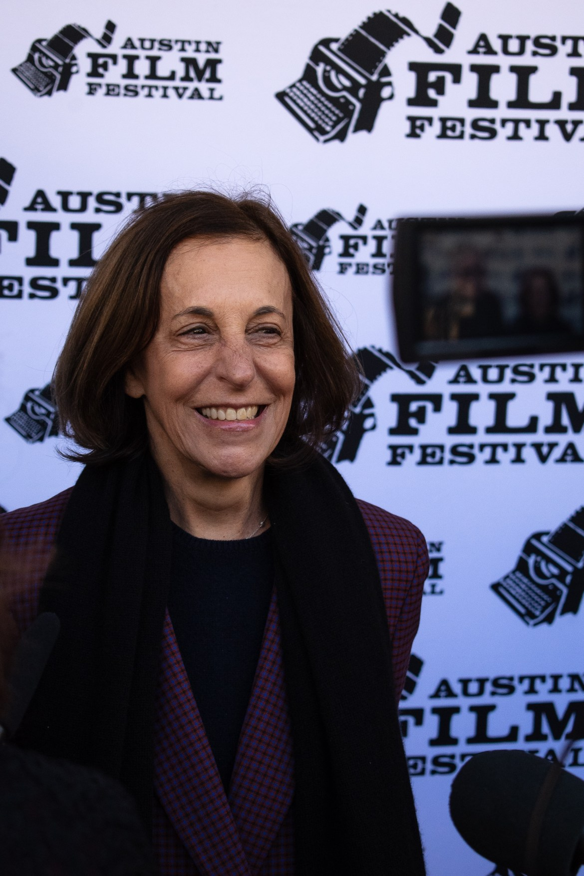 Woman smiles infront of the Austin Film Festival red carpet back drop.