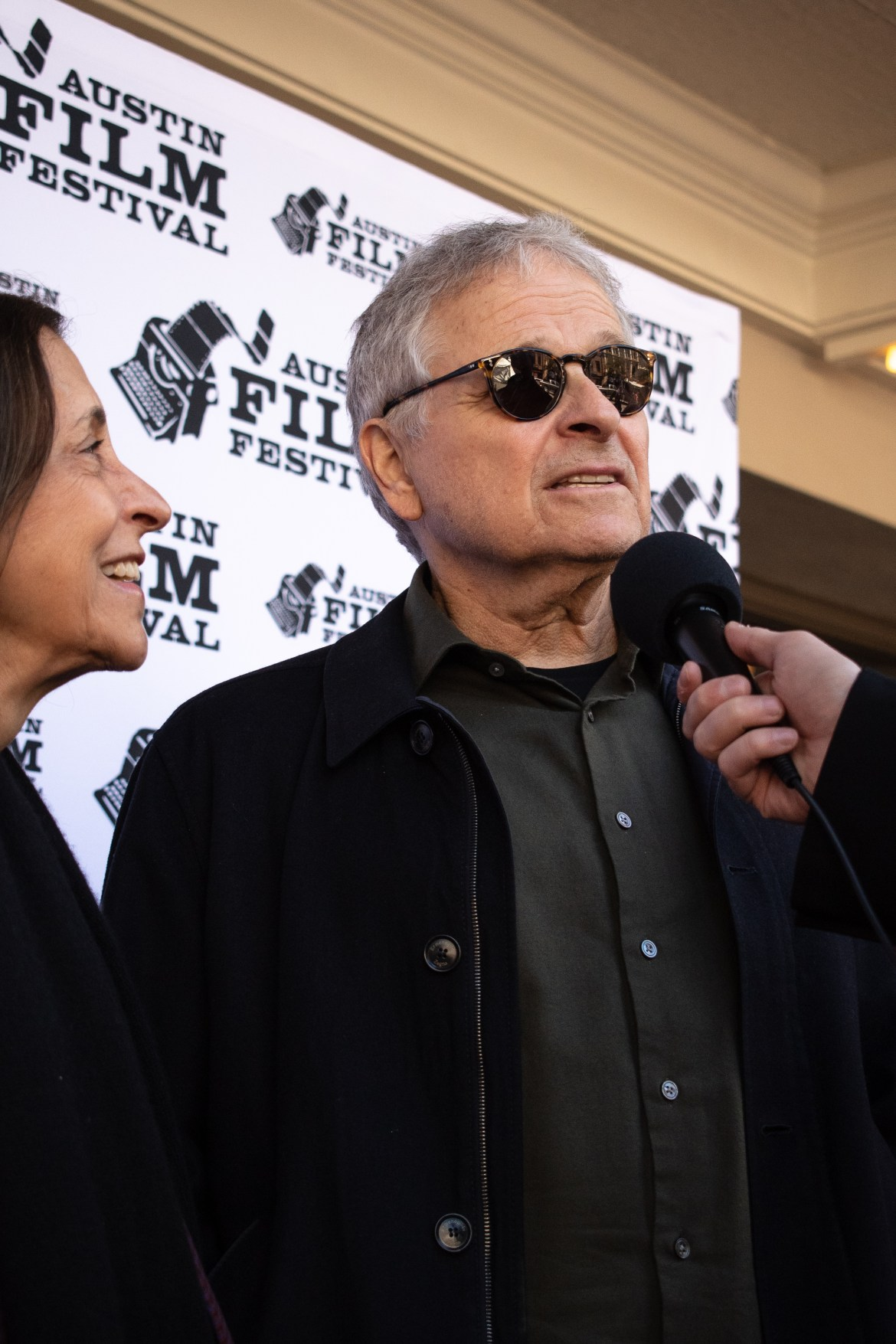 Man stand with a mic held to his mouth by someone off screen. A woman stands off to the left.