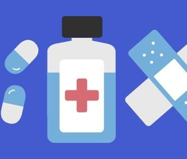 Three medication pills, a bottle of medicine, and a bandaid side by side