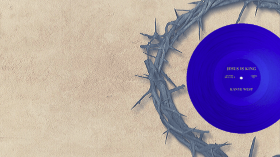 """A royal blue record sits within a crown of thorns, both staged to the right of the photo and a sandy beige background. The record reads in capital gold letters """"Jesus is king"""" top and """"Kanye West"""" on bottom."""