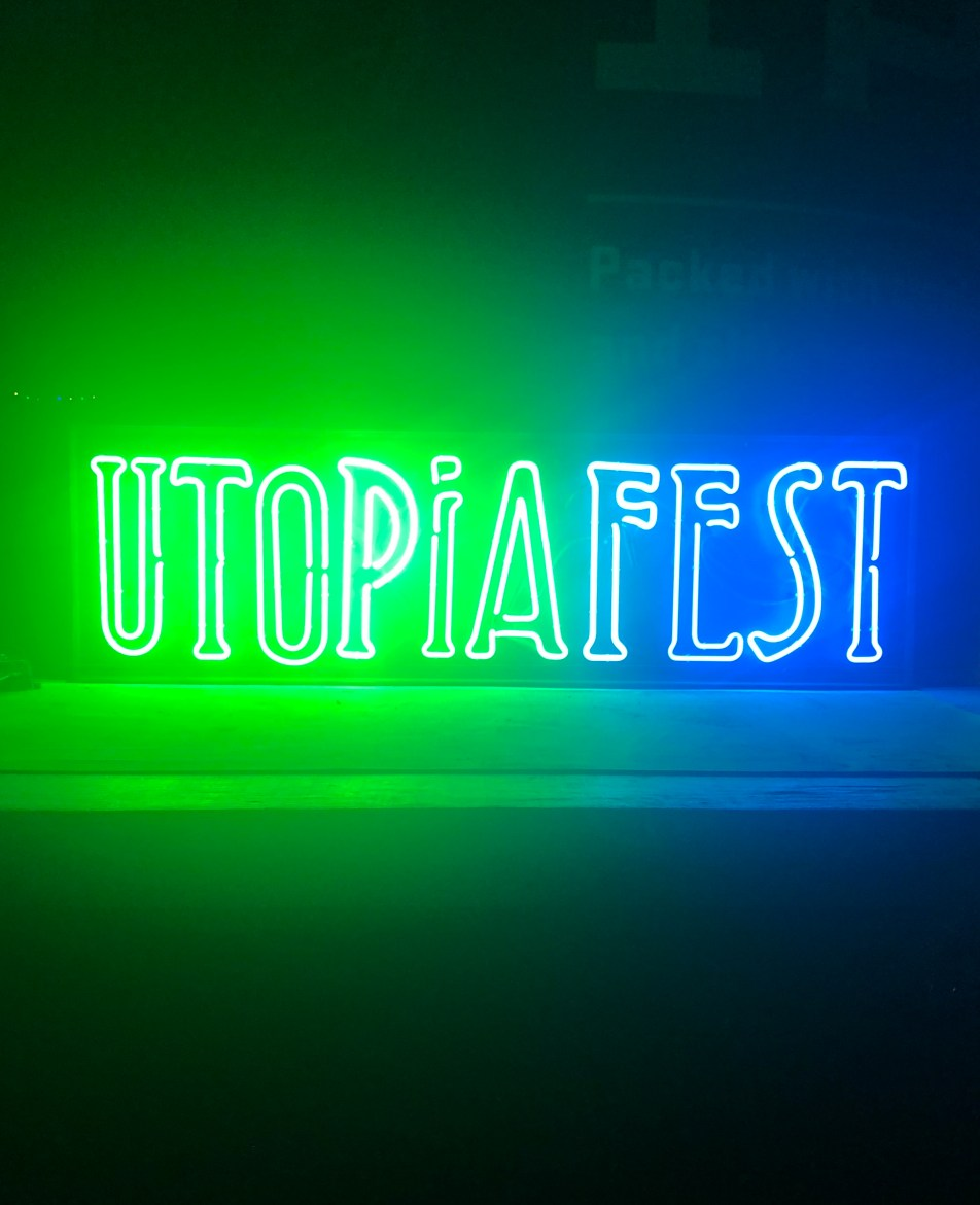 """Neon green and blue light sign that reads """"UTOPIAFEST"""" in darkness."""