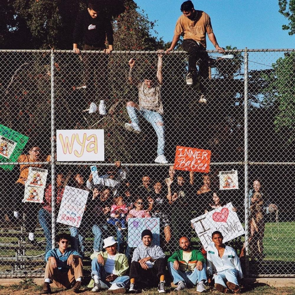 """Behind a fence are several people holding signs saying: """"I love Inner Wave,"""" and """"Inner Babies."""" The band sits on the ground in front of the fence along with one sign mounted on the fence which reads: """"wya."""""""