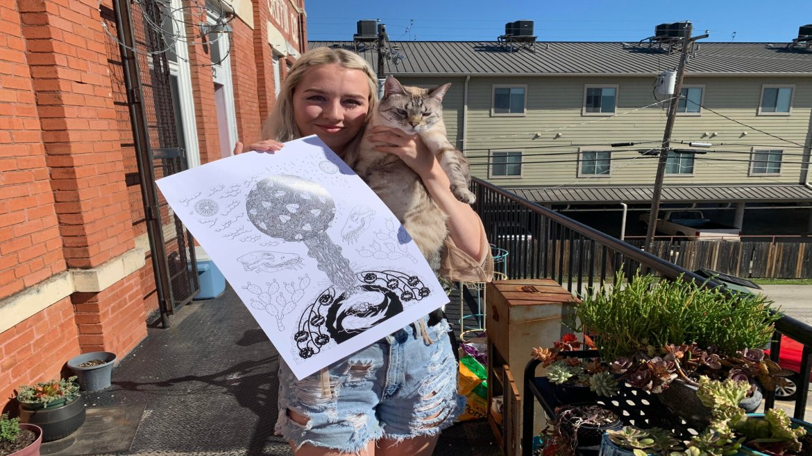 Phoebe Mau outside holding one of her art pieces and her cat, Mika