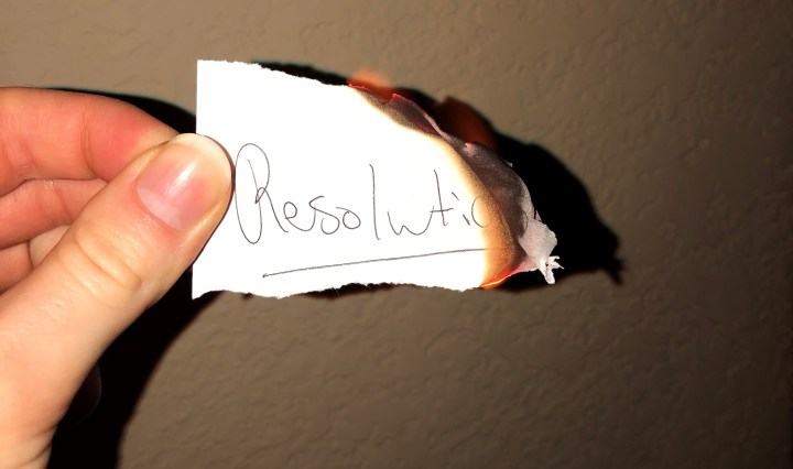a White piece of paper that says resolutions burning.