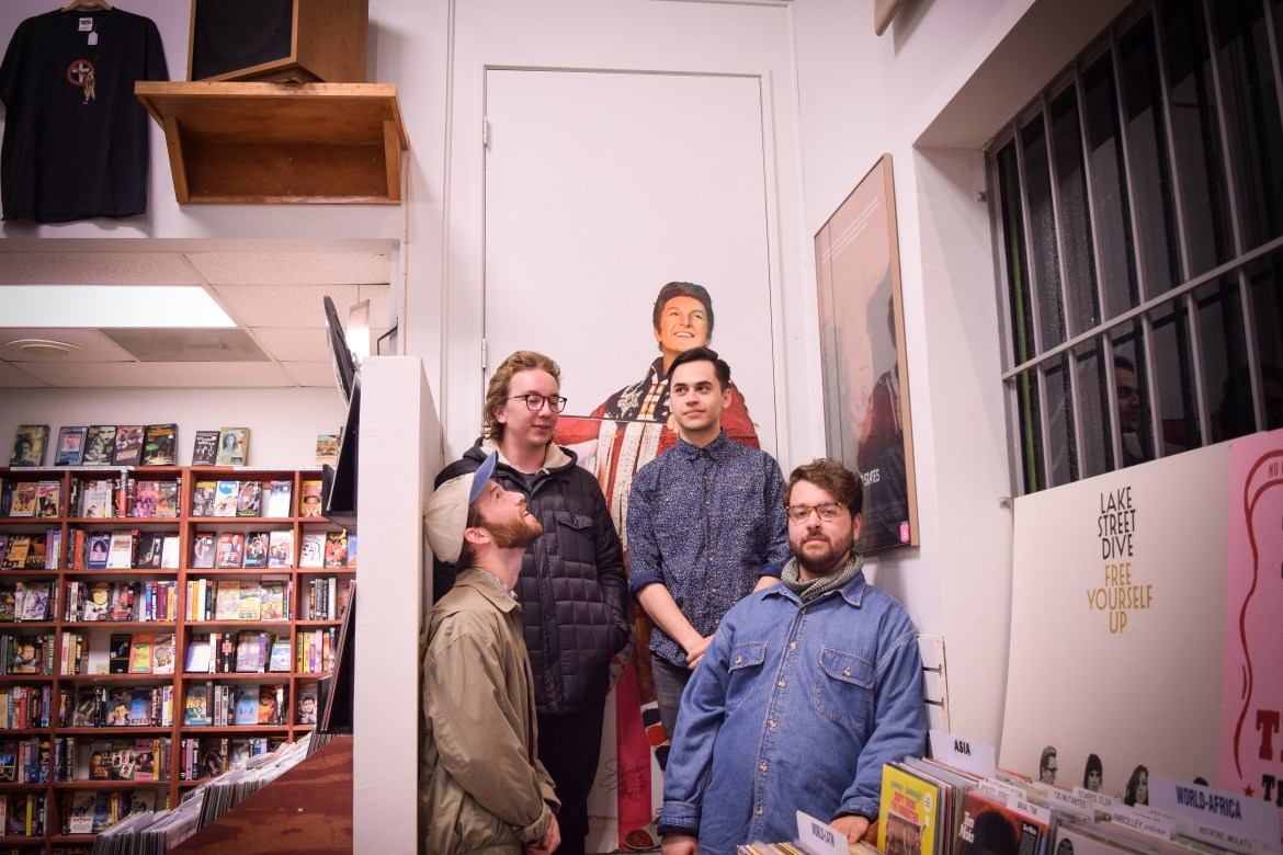 The image featured four males posing together on a small staircase in a record store