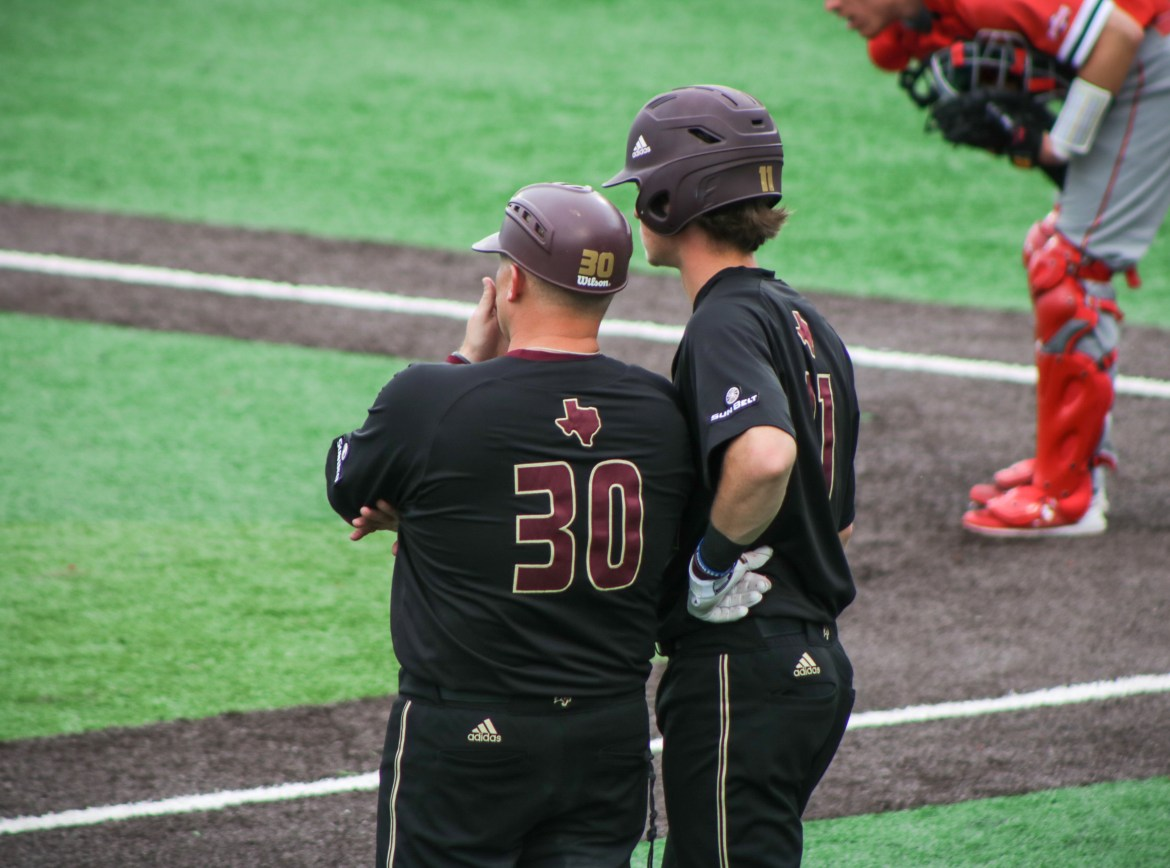 Coach Steven Trout talks with Cameron GIbbons while waiting for the opposing team's pitcher to warm up during a pitching change.