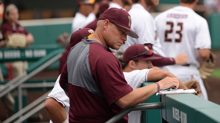 Coach Steven Trout stares at a lineup card, which is placed on the railing of a dugout.