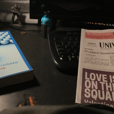 A desk is illuminated by a desk lamp; sitting atop the desk is a college text book and an issue of the University Star.