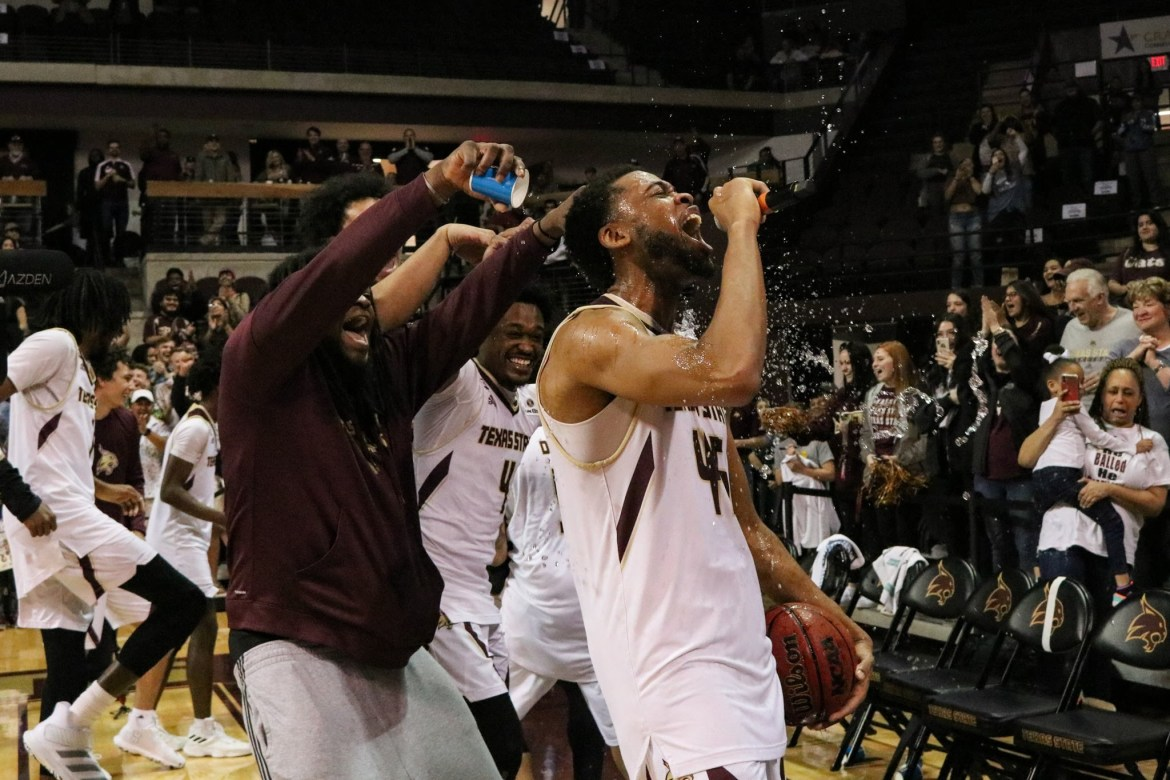 Texas State players pouring water on #45 Eric Terry after winning against Georgia State in Strahan Arena.