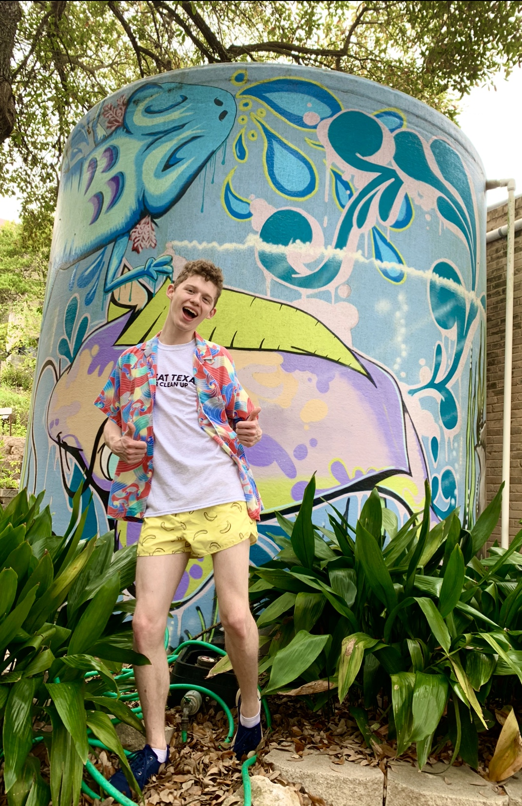 photo of Alex in front of a water tank behind the Hines building on Texas State campus