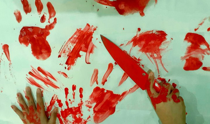 Bloody red handprints on a white background, while a woman hands a shown bloody holding a knife.