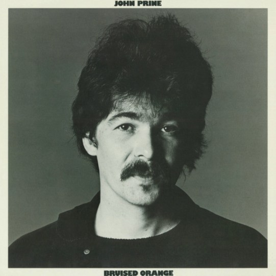 A black and white image of the artist wearing all black. The photo is from the shoulder up. The artist's name is displayed at the top of the image, and the album title is located at the bottom.