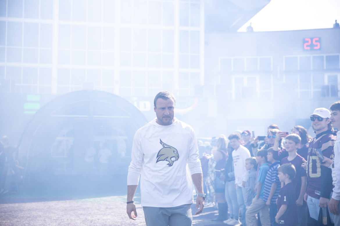Head Coach Jake Spavital is walking out of the tunnel in a cloud of smoke as Texas State fans line the edge of the running out area