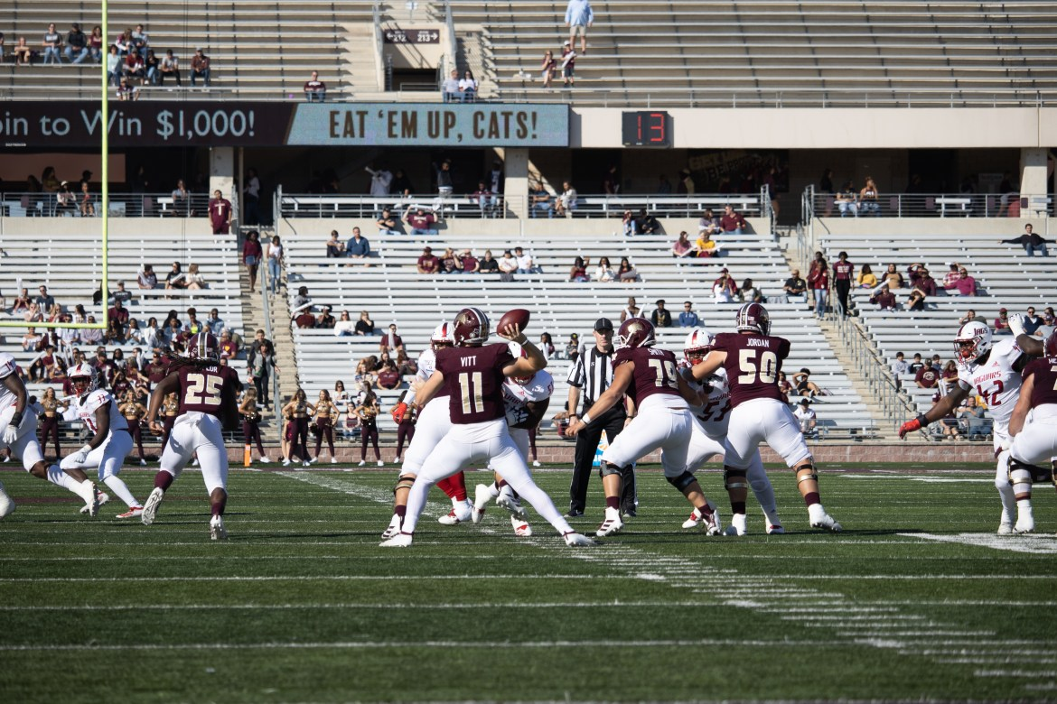 Tyler Vitt is about to throw the ball behind a strong offensive line that hasn't allowed pressure. The north endzone and stands are in the background of the photo
