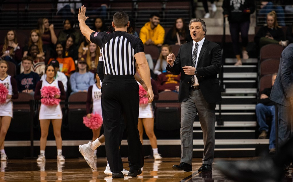 Danny Kaspar in a black suit talks to a nearby referee with forward Isiah Small behind the referee at Strahan Arena in San Marcos, Texas.