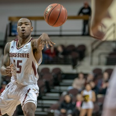 Jaylen Shead in a white and maroon Texas State jersey passes the ball to a teammate during a basketball game at Strahan Arena in San Marcos, Texas.