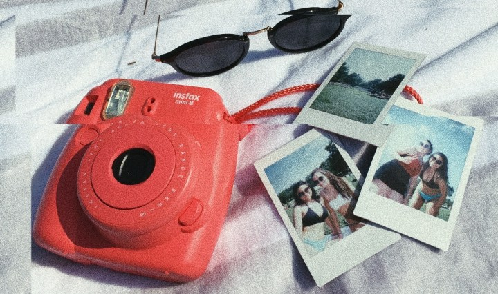 There is a pair of black sunglasses with gold accents, a coral pink polaroid camera, and three polaroid pictures on top of a grey and white striped towel. One of the polaroids shows the landscape of the San Marcos River, and the other two pictures show smiling girls wearing swimsuits.