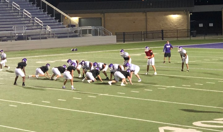 The San Marcos High School football offense prepares to run a play against their defense at practice.