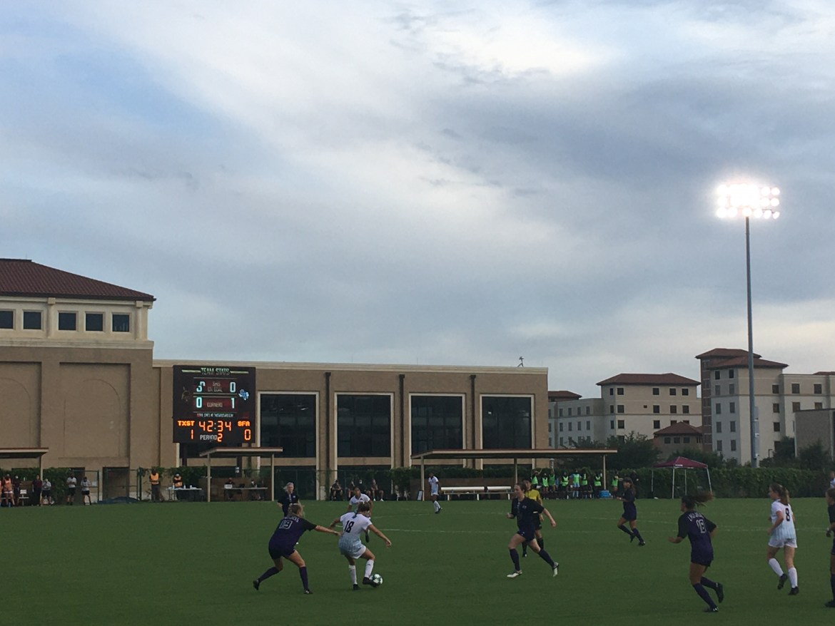 Senior Mackenzie Smith while being pressed passes the ball to a teammate in the match vs. Stephen F. Austin, the Bobcats are wearing white jerseys with teal accents. SFA is wearing purple jerseys with black sleeves. It is early evening the lights are on to start illuminating the field, the campus Rec Center can be seen in the background.