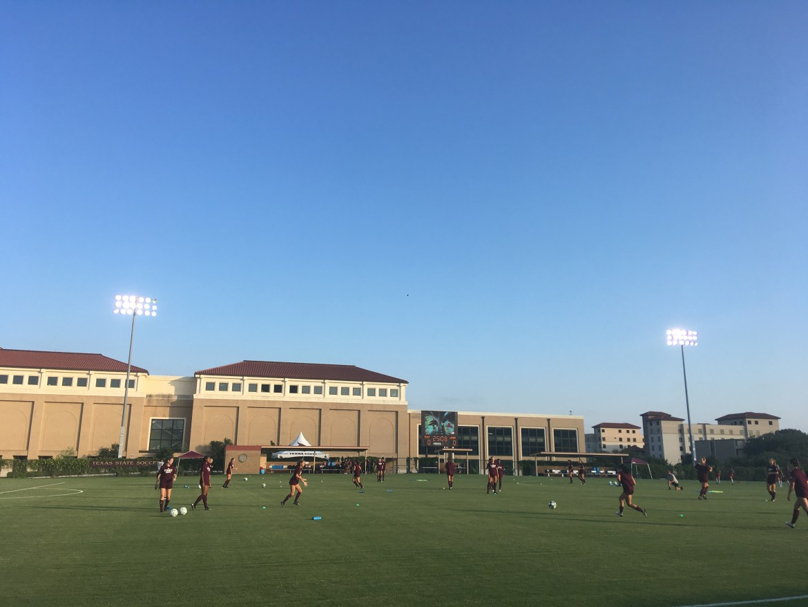 he Bobcats warm-up for a match Alt-text: The Bobcats doing a drill to warm up pre-game, multiple players pictured wearing their maroon warmups and passing the ball in formation.