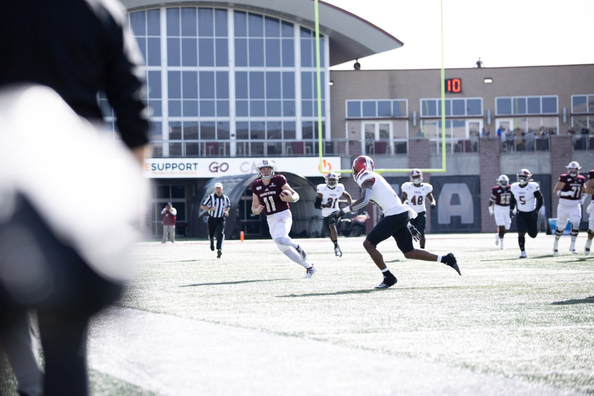 Texas State quarterback Tyler Vitt scrambles versus Troy in 2019 matchup. A Troy defender is in pursuit of Vitt.