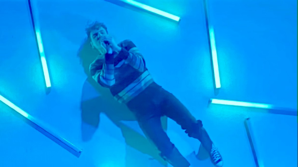 """Lead singer, Chase Lawrence, singing """"Boyfriend"""" surrounded by blue lights"""