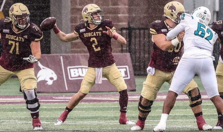 Texas State quarterback Brady McBride is throwing a pass versus Coastal Carolina. He is about to release the ball. He is in Texas State's maroon and gold jerseys with a gold helmet.