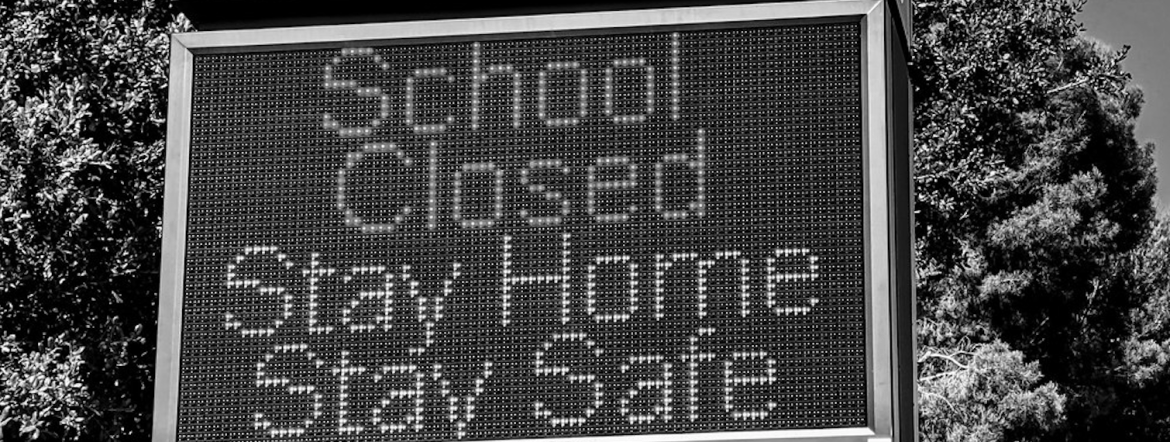 """A Black and White picture of a billboard with the words: """"Schools Closed, Stay Home Stay Safe"""" written. There is a tree in the background."""