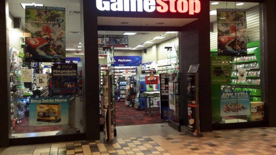 Photo showing GameStop logo at the top of the store. Mario Kart 8 posters are displayed on the left and right windows. Inside of the store is well lit with the PlayStation banner hanging in the background. Inside of the store are lots of games on the racks.