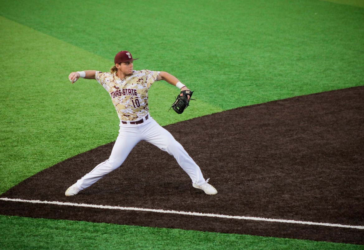 : A baseball player wearing a gold, white and maroon pixelated jersey and white pants extends his arm to throw a baseball.