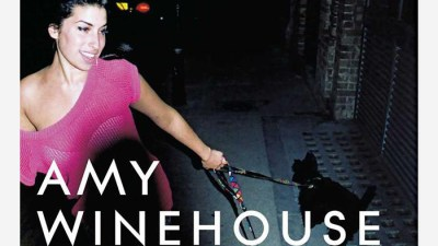 """Amy is dressed in a pink top and is smiling. She is holding a leash with her left hand which has a black dog on the end of it. The text """"Amy Winehouse"""" is present in white text while Frank is present in pink text to match her shirt."""