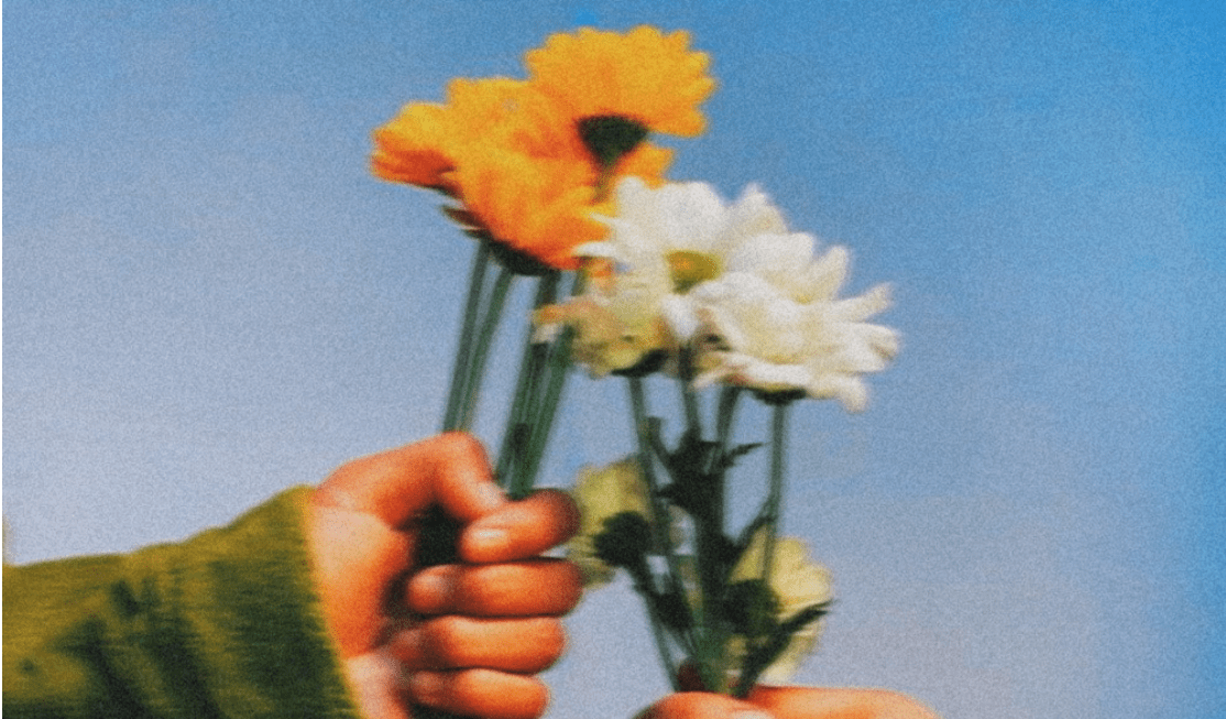 Two hands holding flowers