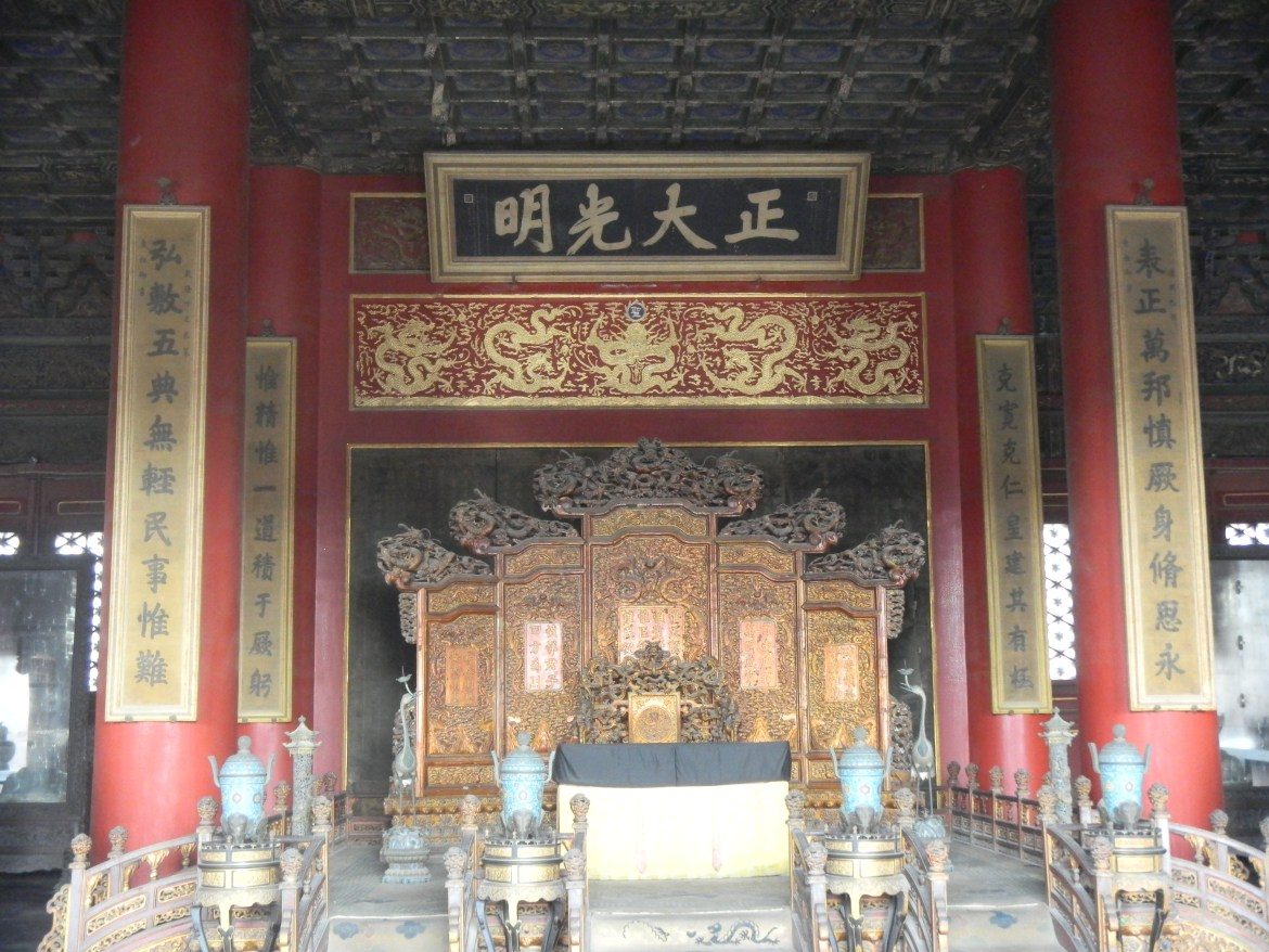 The throne of Chinese emperors during the Qing Dynasty period (1644-1912). The throne is gold, many Chinese characters and a low cushion.