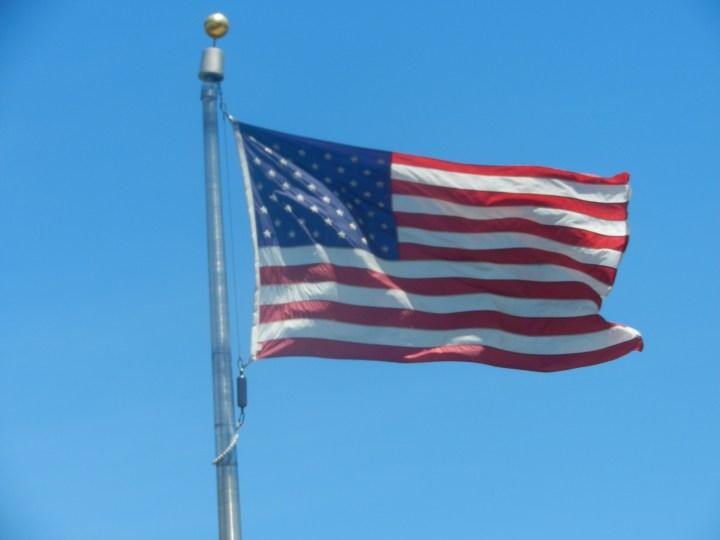 A photo of a U.S. flag flowing in the wind on a pole.
