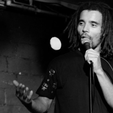 Akala is standing on stage in front of a brick wall, holding a microphone.
