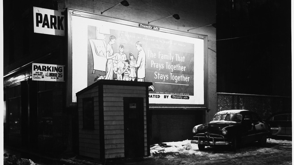 A black and white photo of a billboard that shows 3 children with their parents on their knees praying together with a caption next to them saying: The Family That Prays Together Stays Together. Also, this looks to be a picture taken at night with a car from the 1950's era off to the side.