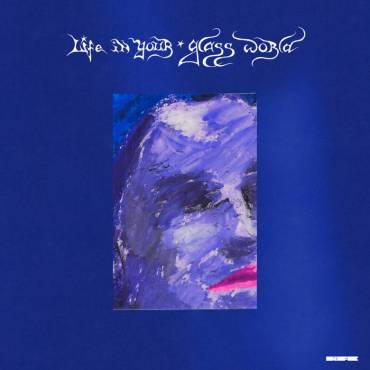 This is a photo of Citizen's Life In Your Glass World album cover which has a purple-painted face surrounded by a blue background.