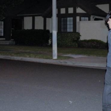 A man walking in a dark neighborhood looking behind him.