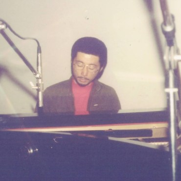 A picture of a Younger Ryo Fukui sitting by a piano with some microphones in view