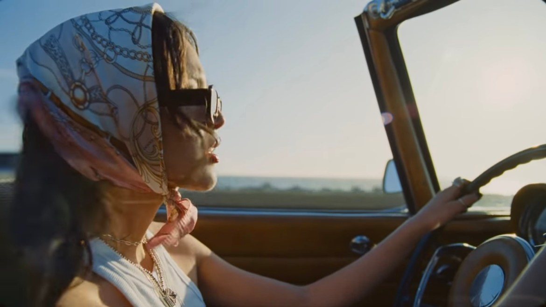 Image of Olivia Rodrigo's side profile driving by a beach