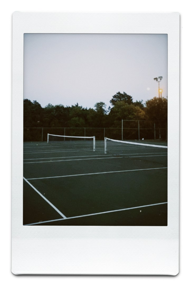 : photo of an empty tennis court at dusk