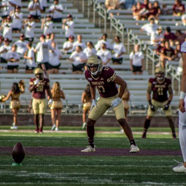 football player in white uniform and green helmet getting ready to kick the ball to Bobcat football players in maroon jerseys, gold pants, and gold helmets.