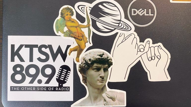 """Photo of various stickers adhered to the bottom left corner of a Dell laptop. Stickers include from left to right a square black and white sticker reading """"KTSW 89.9 the other side of radio"""" with a microphone, an Italian Renaissance depiction of Cupid holding a bow, a black and white illustration of a planet resembling Saturn, a portrait of David by Michelangelo and a line drawing of two hands wrapping their pinky fingers around each other."""